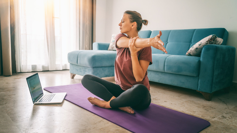 Woman performing a static stretch in her living room