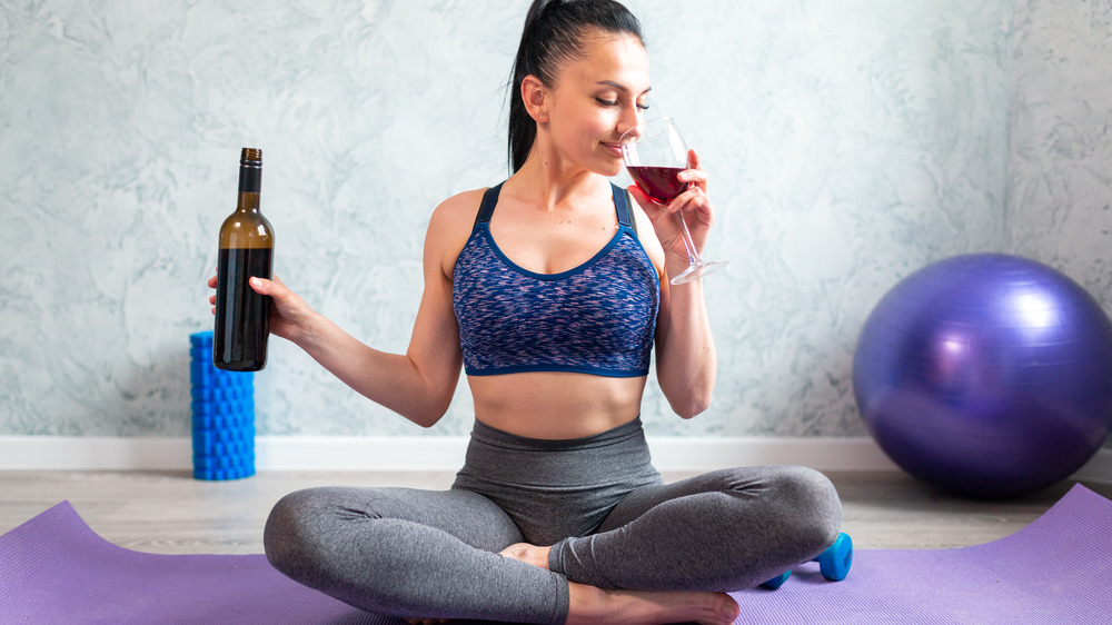fit woman drinking red wine