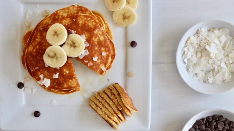 Stack of golden brown pancakes on a white plate