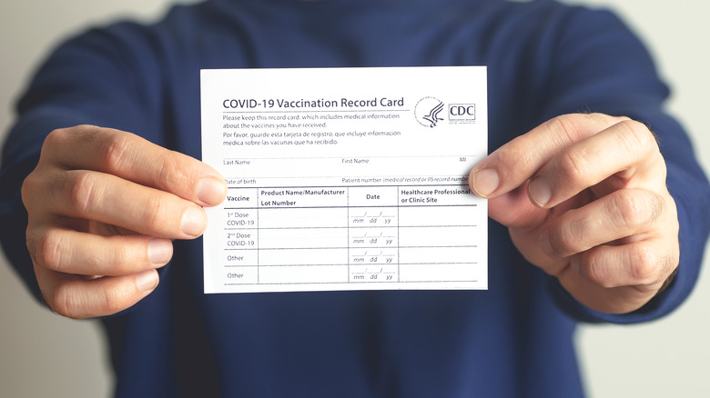 COVID-19 vaccine card displayed by two hands