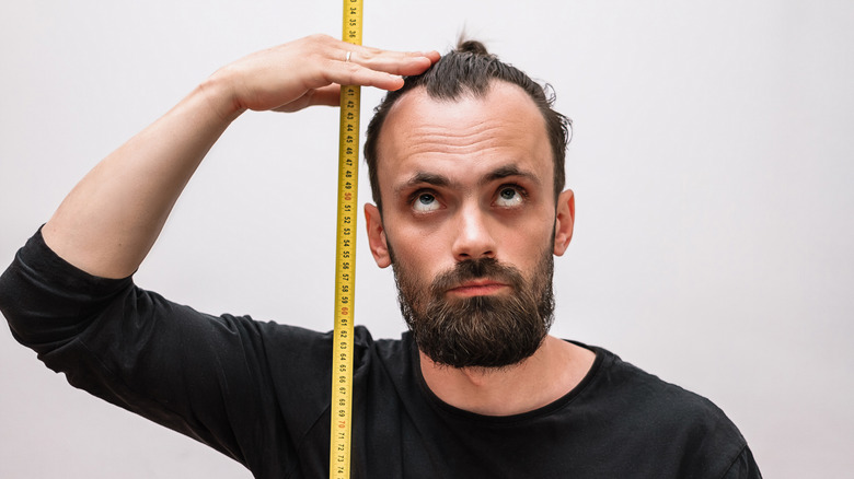 A man measures himself with a tape measure