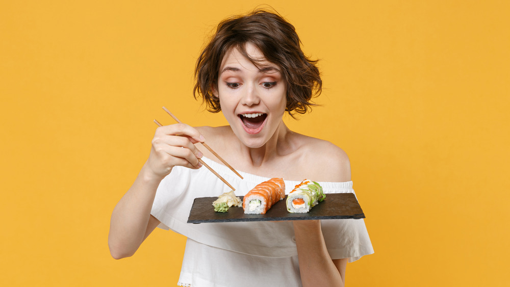 woman using chopsticks, sushi