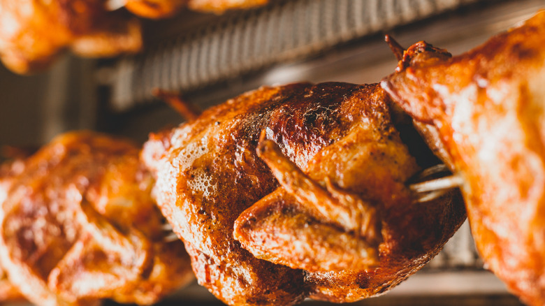 Rotisserie chickens in a large broiler at a store