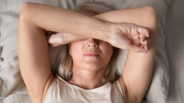 Woman laying down in bed covering her head with her arms in pain