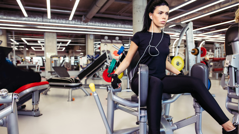 Woman using hip abductor machine