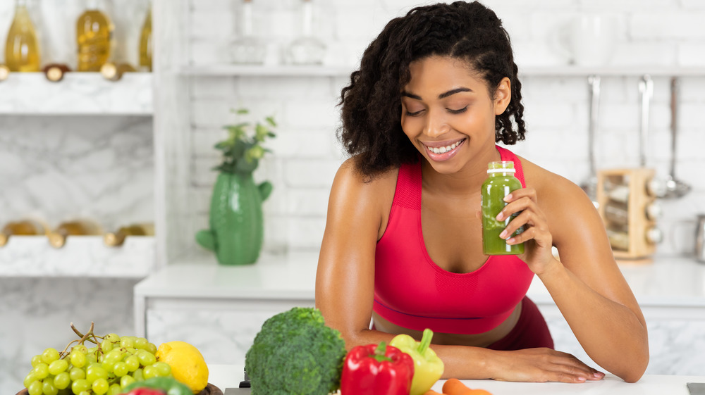 woman holding green juice