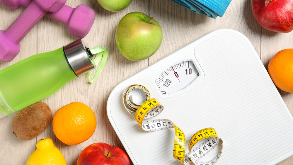 A scale next to fruits and exercise-related items