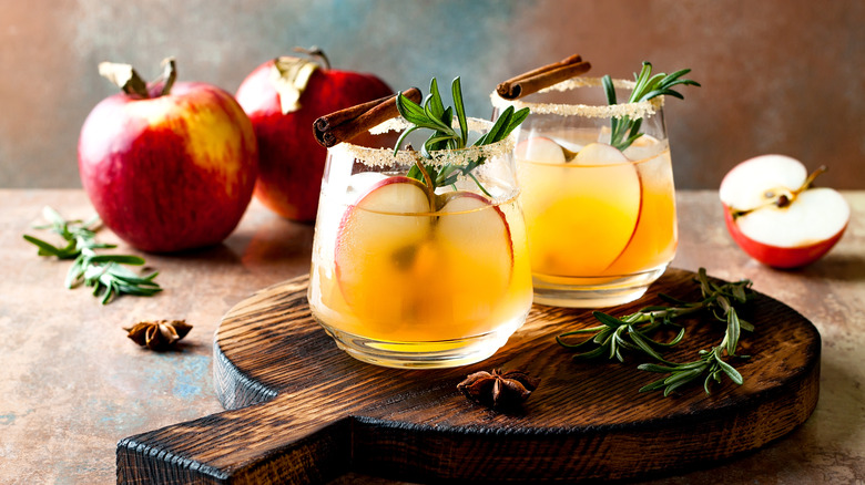 Decorative, spiced apple cider vinegar drinks on wooden cutting board