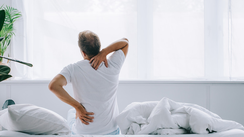 backside view of an older man cracking his own back on his bed