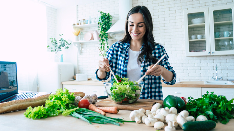 A woman is preparing a salad at home