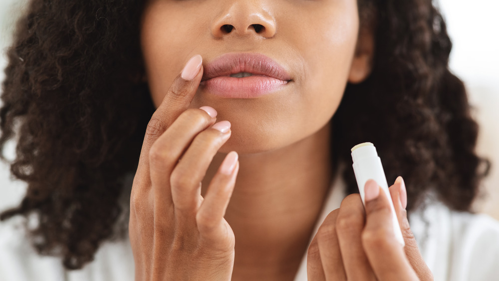 A woman applying lip balm