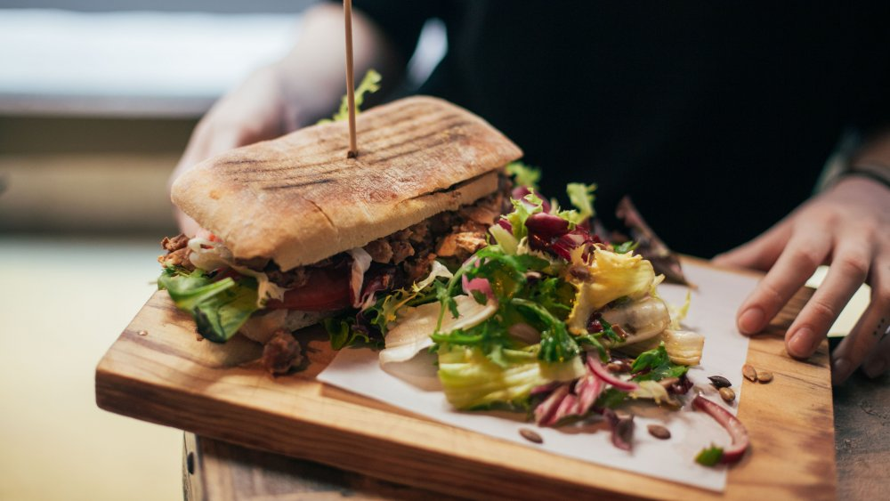 A person's hands holding a large plate with a sandwich and salad