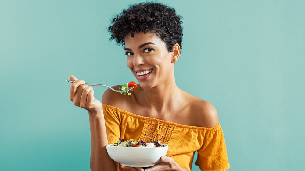 A smiling woman eating a salad