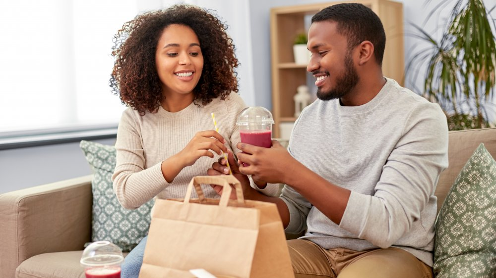 A couple with takeout smoothies sitting on a couch