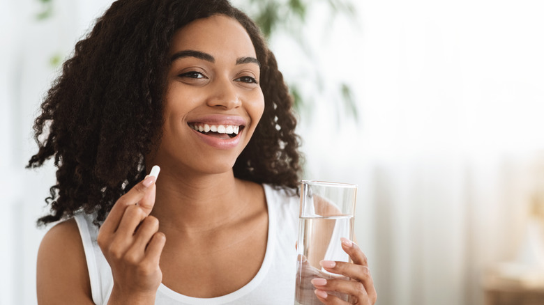 Woman takes vitamin with glass of water.