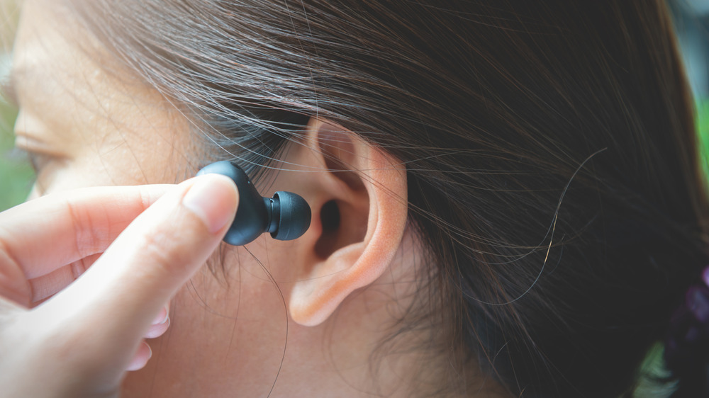 Close up of woman putting in earbuds