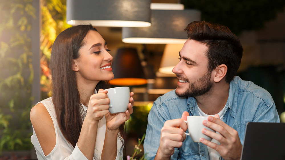 Young couple flirting and drinking coffee