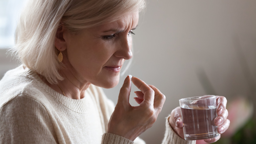 Older woman taking a pill and looking worried