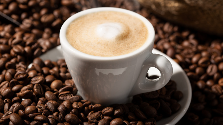 Close up of cup of coffee with milk on bed of coffee beans