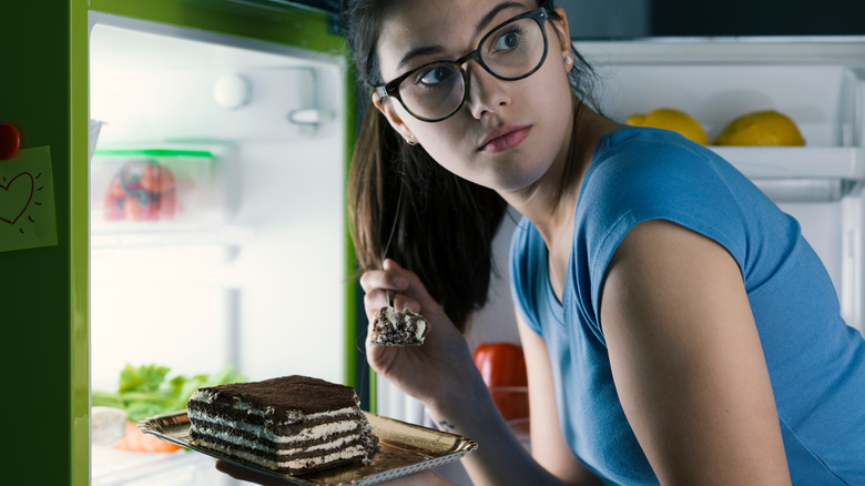 A woman is sneaking cake from the refrigerator.