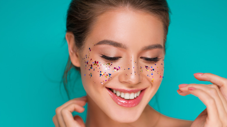 Woman with glitter on her cheeks blushing with blue green background