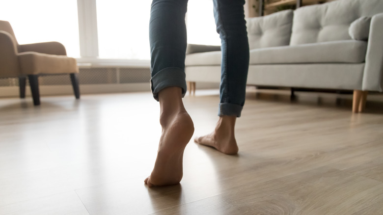 Close-up of a person's feet as they walk across their living room floor