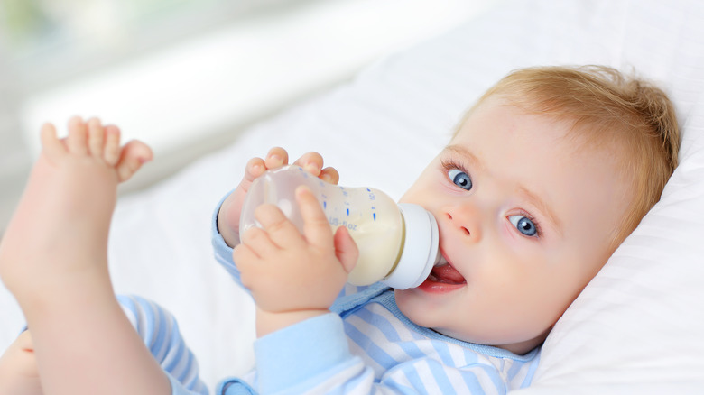 Baby lying down drinking from a bottle