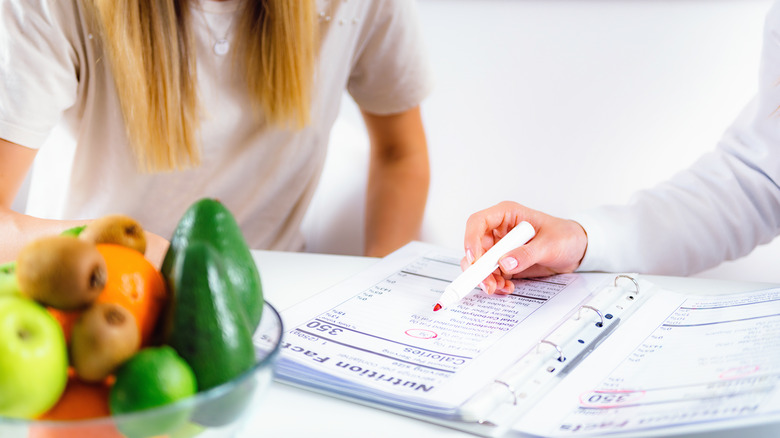 Woman coaching another woman on nutrition facts at a desk with fruit