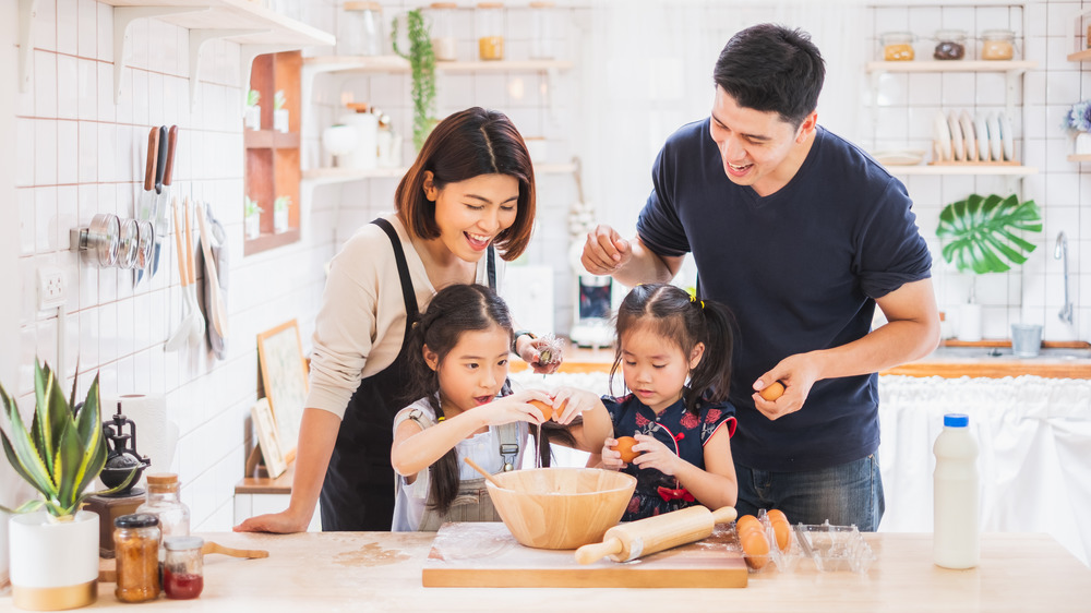A family cooking together in the kitchen, happily