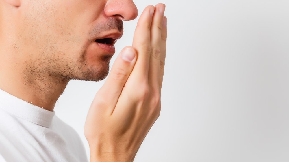 Man in white shirt checking his breath with his hand