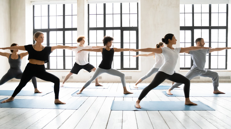 Group of people doing warrior two pose in yoga class