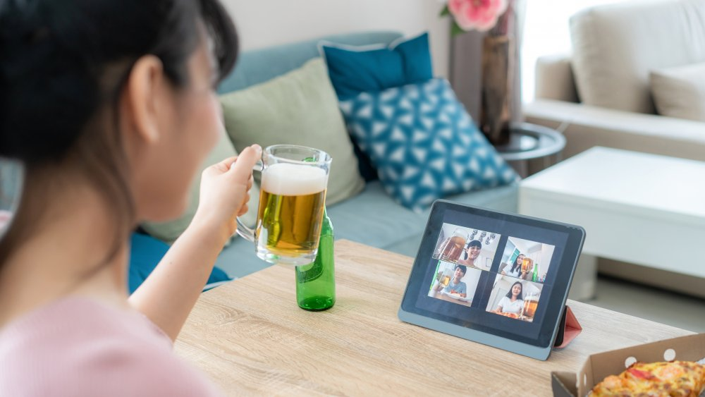 Woman drinks beer on a video call
