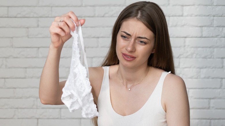 Woman holding up a white pair of underwear