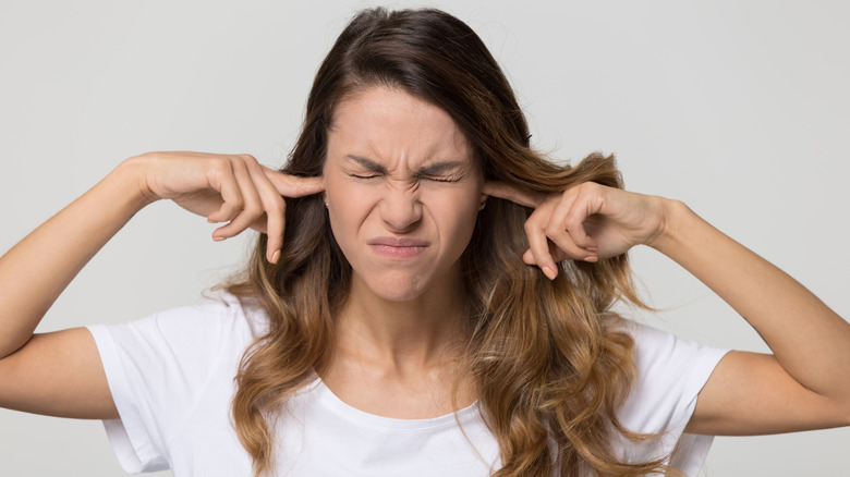 Woman frowning holding her fingers to her ears