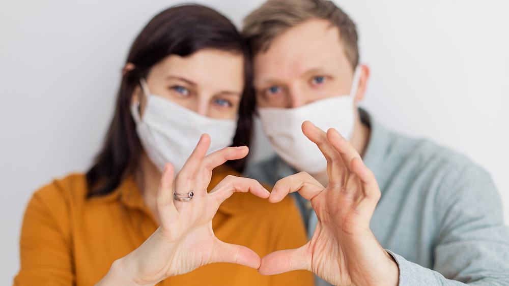 Masked couple forming heart symbol