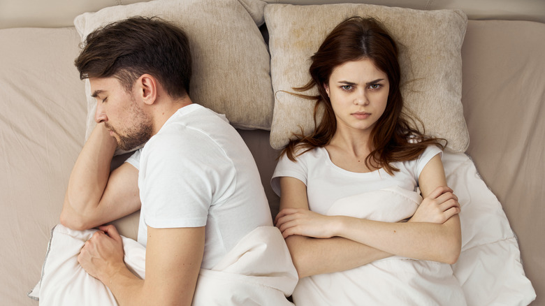 Couple in bed, woman is angry