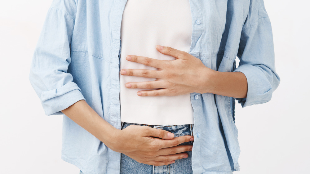 smiling woman holding stomach