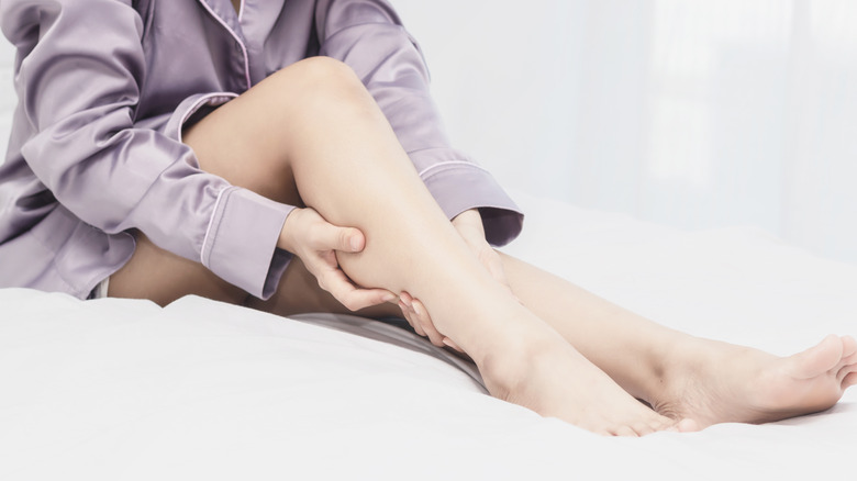 woman holding leg in bed