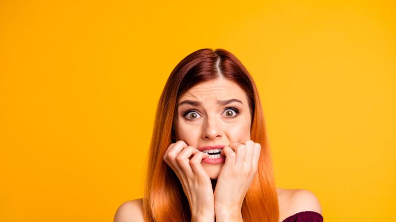 Young scared woman on yellow background