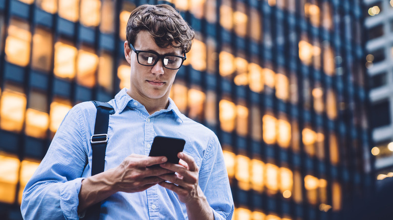 man in glasses texting on a phone