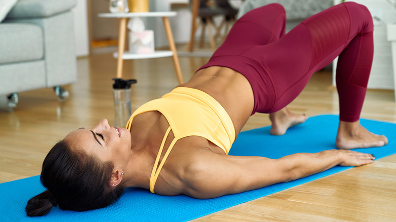 A woman in exercise clothes doing a hip bridge in her living room