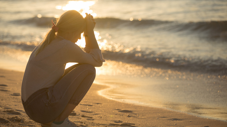 sad woman sitting at edge of ocean