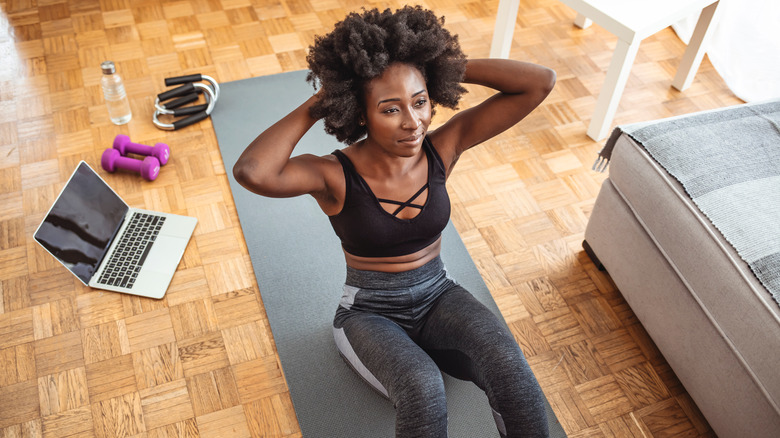 Woman dressed in black sports bra and grey leggings doing sit up on yoga mat