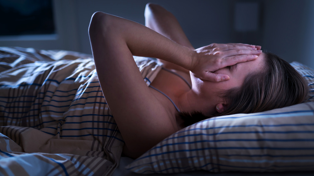 Woman laying in bed at night with her hands over her eyes