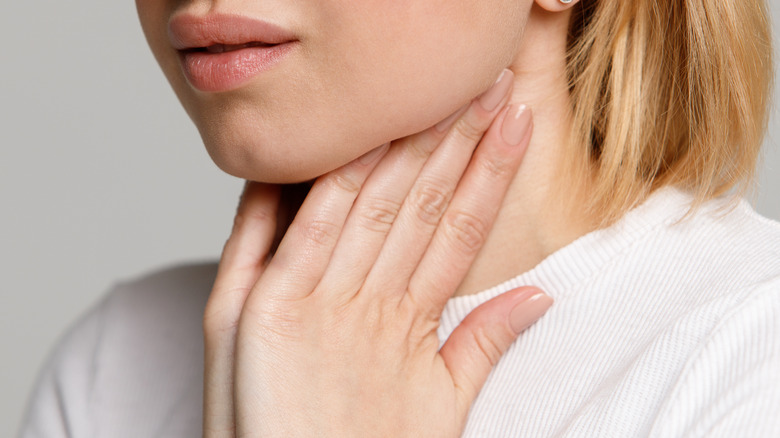 Close up of young woman feeling lymph nodes on her neck