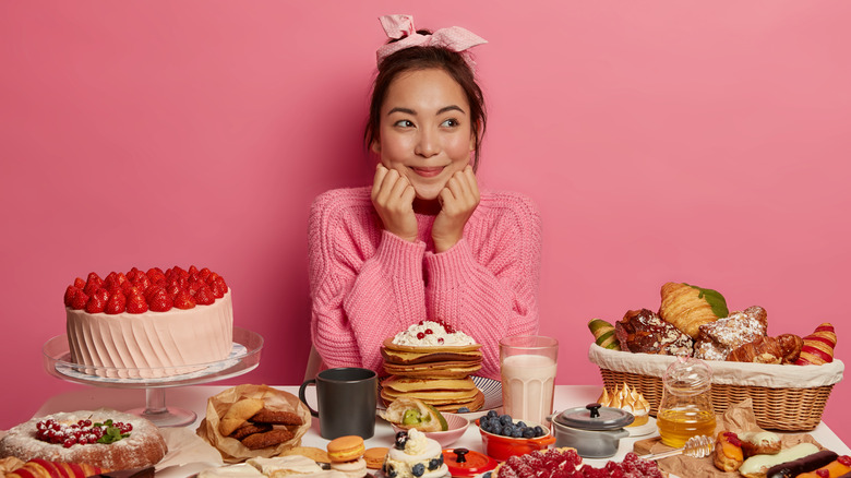 smiling woman behind a table of sweets with an all pink background