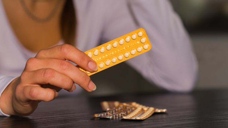 A woman holding a pack of contraceptive pills