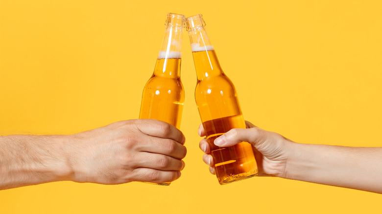 man and woman's hands, clinking beer bottles