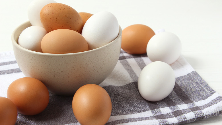 Bowl of white and brown eggs with some on table