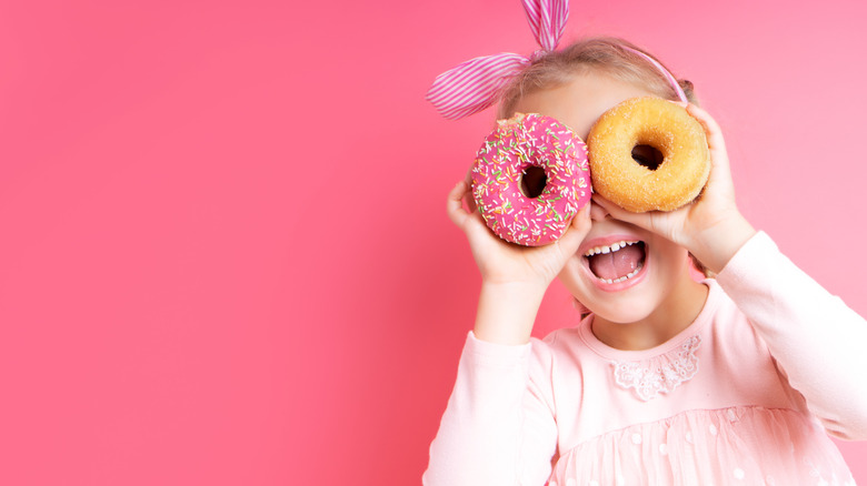 A young girl using donuts as glasses with an all pink background